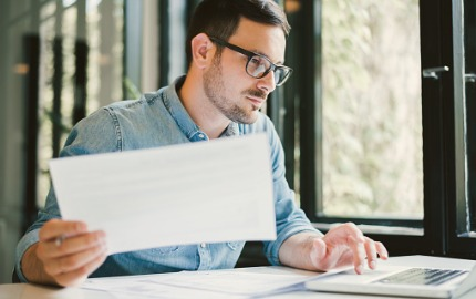 Mann kalkuliert Kosten am Laptop