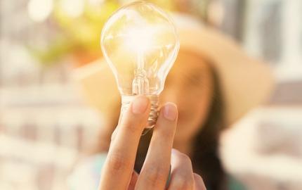Frau hält Glühbirne